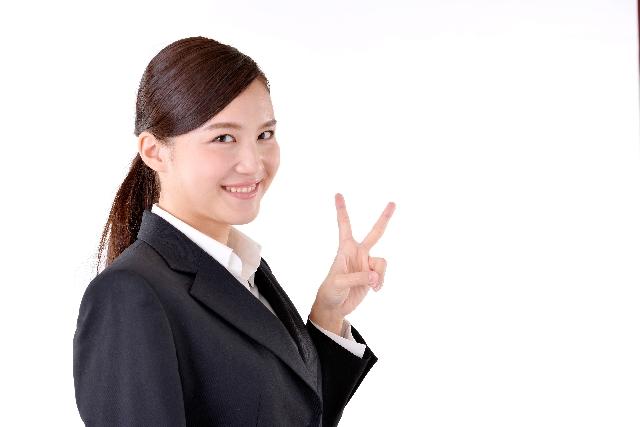 ピースサインを出すスーツ姿の女性