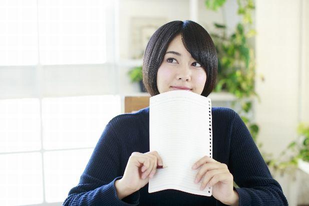 ノートを持って考える少女