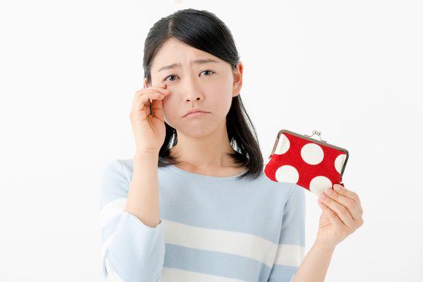 財布の中身を覗き込んで、必要なお金が全然足りなくて嘆き悲しむ専業主婦
